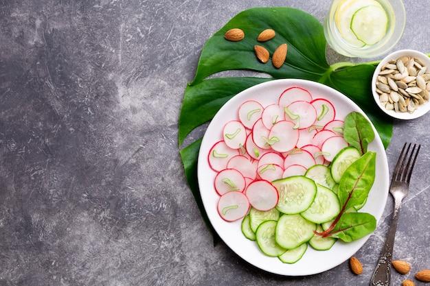 Lekka sałatka z rzodkiewki z ogórkiem, napój detox z cytryną, migdałami i pestkami dyni na szarej powierzchni. koncepcja zdrowego odżywiania.