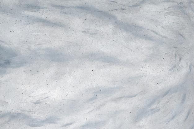 Lekka ściana z abstrakcyjnymi szarymi wiruje na białej, otynkowanej powierzchni z kopią