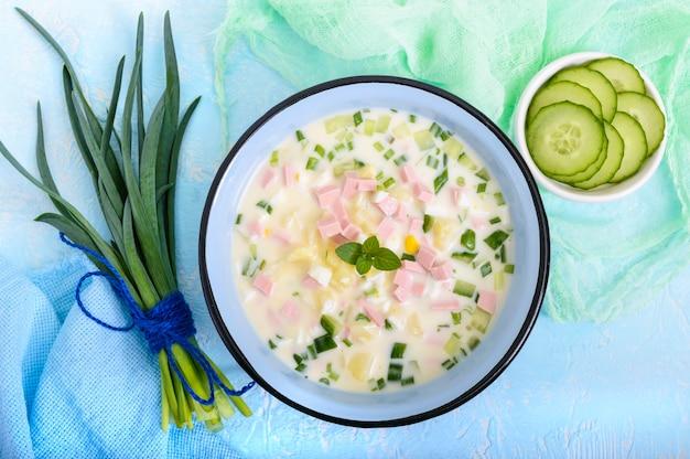 Lekka zupa dietetyczna ze świeżymi ogórkami, doprawiona jogurtem w miseczkach na jasnym tle.