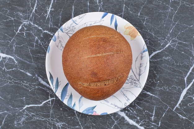Lekki bochenek chleba na talerzu, na marmurowej powierzchni