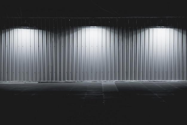 Lekki pudełko z metal ściany platformą dalej z światłami reflektorów, lampy wiesza na ściennym tle