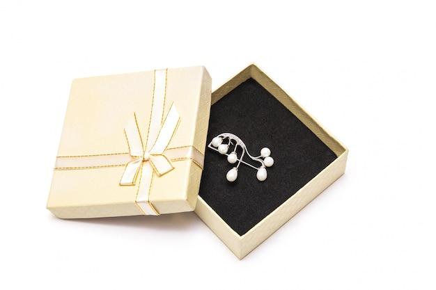 Lekki teraźniejszości pudełko z srebną broszką na białym tle. pojedynczo na białym. biżuteria w pudełku