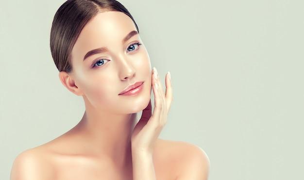 Lekki uśmiech na idealnej twarzy młodej ładnej kobiety oraz elegancka kosmetologia gestów i pielęgnacja twarzy