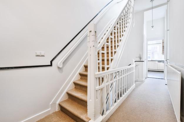 Lekki, wąski korytarz z białymi schodami i ogrodzeniem w domu o kilku kondygnacjach