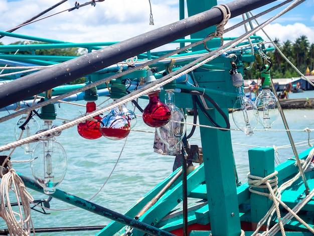 Lekkie lampy i wiele niechlujnych lin na drewnianej lokalnej łodzi rybackiej w doku z bliska