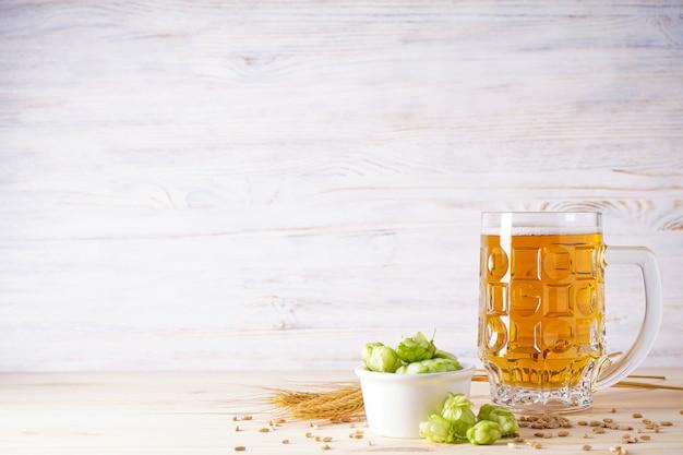 Lekkie piwo w szklance i szyszki chmielowe