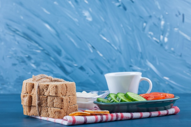 Lekkie śniadanie, filiżankę herbaty, miskę pokrojonego ogórka i pomidorów oraz chleb na ściereczce, na niebieskim stole.