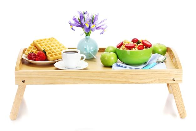 Lekkie śniadanie na drewnianej tacy na białym tle