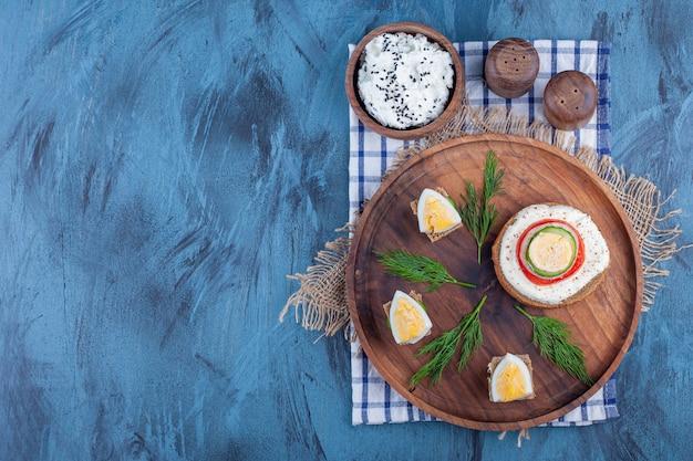 Lekkie śniadanie na drewnianym talerzu na kawałkach tkaniny na niebiesko.