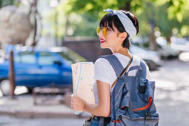 Lekko opalona brunetka nosi modne dodatki, rozglądając się z zakłopotaniem, trzymając w ręku mapę miasta