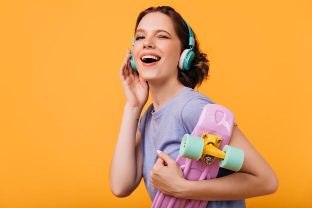 Lekko opalona wesoła dziewczyna pozuje z różowym longboardem. kryty zdjęcie śmiejącej się ładnej pani w dużych słuchawkach na białym tle.