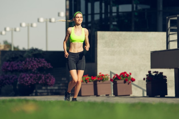 Lekkoatletka biegaczka trenuje na zewnątrz w słoneczny dzień lata summer