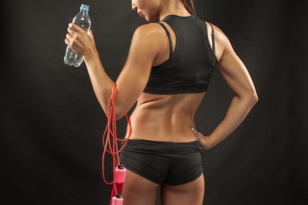 Lekkoatletka mięśni młoda kobieta z skakanka na czarno