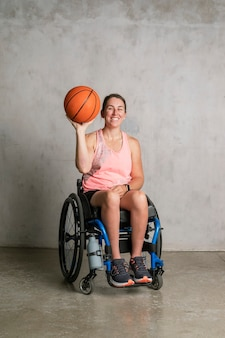 Lekkoatletka na wózku inwalidzkim trzymająca piłkę do koszykówki