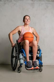 Lekkoatletka na wózku inwalidzkim z piłką do koszykówki