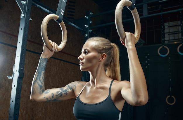 Lekkoatletka w czarnej odzieży sportowej, stojąc na siłowni, trzymając pierścienie zanurzeniowe i odwracając wzrok