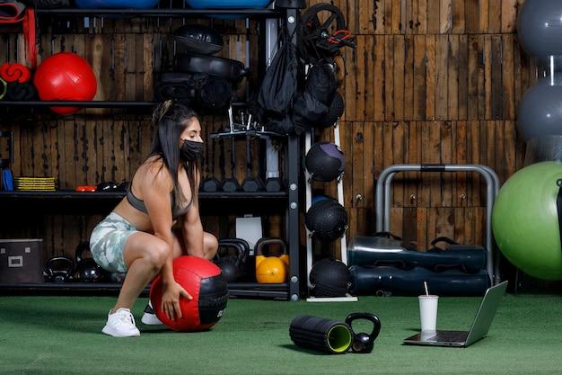 Lekkoatletka z ciężarami uczy online z komputerem w masce dla nowej normy