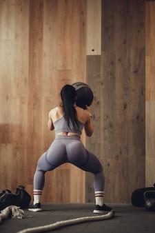 Lekkoatletka z napompowaną pupą przysiada z fito piłką pod ścianą