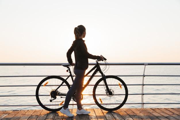 Lekkoatletyczna kobieta stojąca z rowerem na promenadzie, podczas wschodu słońca nad morzem
