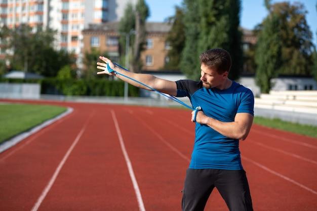 Lekkoatletycznego mężczyzna brunetka robi trening z elastycznym ekspanderem na stadionie w słoneczny dzień. pusta przestrzeń