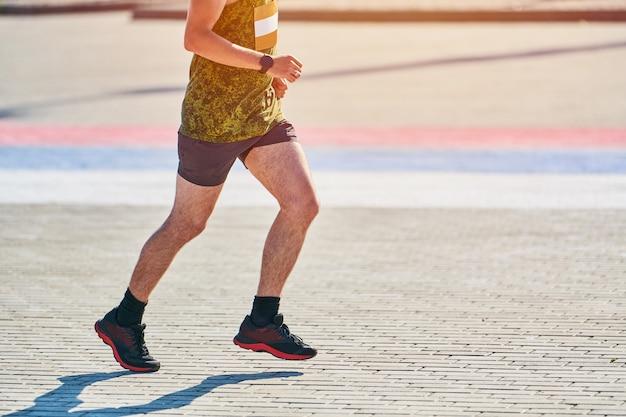 Lekkoatletycznego mężczyzna jogging w odzieży sportowej na drodze miasta