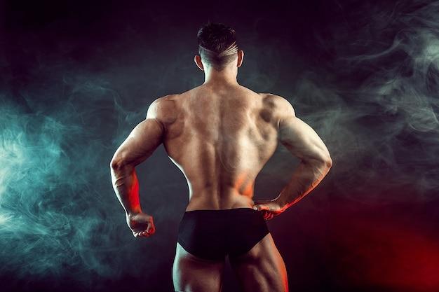 Lekkoatletycznego mężczyzna napina mięśnie dymem. silny kulturysta z doskonałymi mięśniami brzucha.