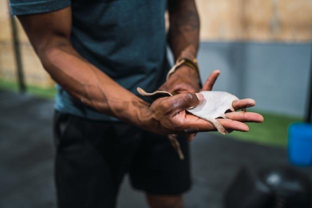 Lekkoatletycznego mężczyzna przygotowuje się do treningu crossfit.