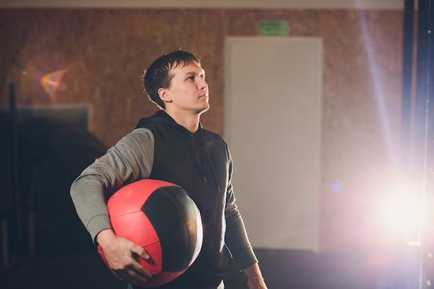 Lekkoatletycznego mężczyzna robi brzuch ćwiczenia na podłodze. obsługuje robić treningowi używać medycyny piłkę przy gym.
