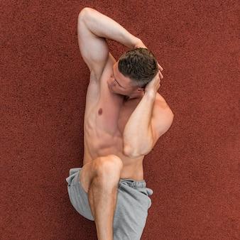 Lekkoatletycznego mężczyzna robi ćwiczenia abs