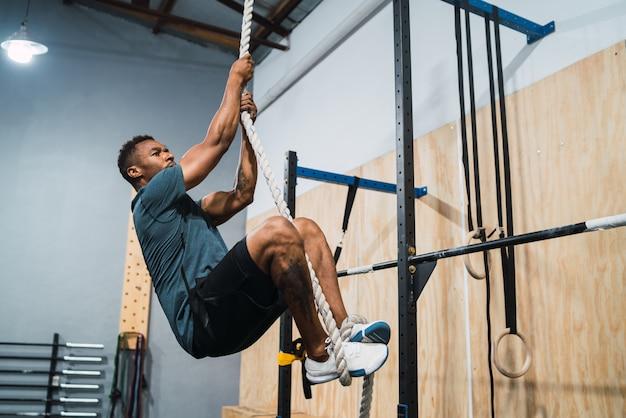 Lekkoatletycznego mężczyzna robi ćwiczenia wspinaczkowe.
