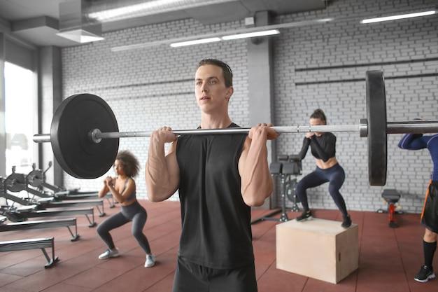Lekkoatletycznego mężczyzna treningu ze sztangą w nowoczesnej siłowni
