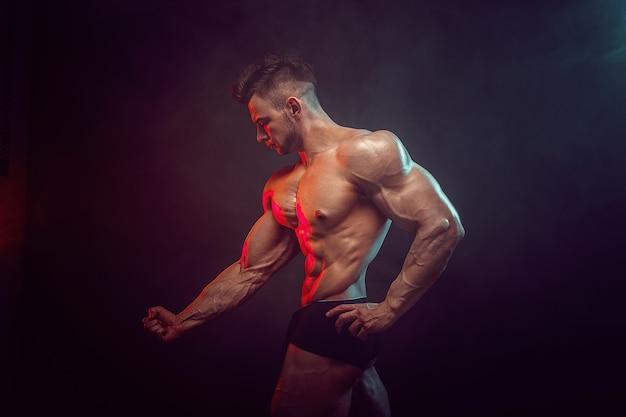 Lekkoatletycznego mężczyzna zginanie mięśni w studio na ciemnej ścianie z dymem. silny kulturysta z doskonałymi mięśniami brzucha.