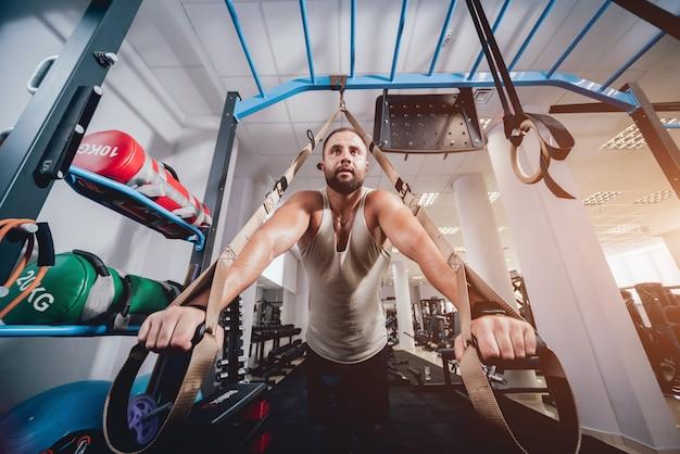 Lekkoatletycznego młody człowiek szkolenia z trx fitness pasy.