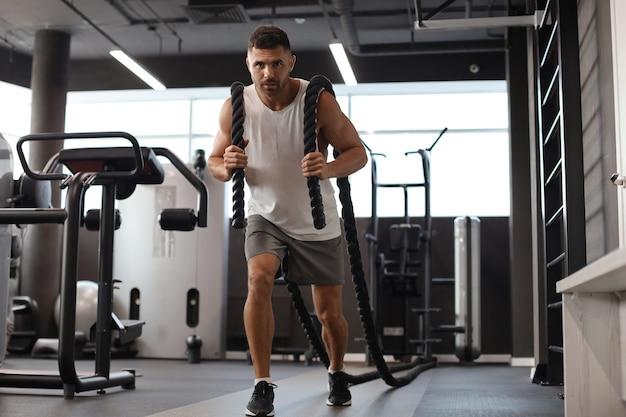 Lekkoatletycznego młody człowiek z liny bojowej robi ćwiczenia w siłowni fitness trening funkcjonalny.