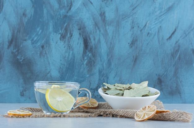 Lemoniada i pokrojona sucha cytryna obok miski liści na ręczniku na marmurze.
