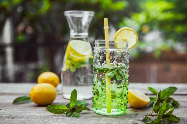 Lemoniada i składniki w szklanym dzbanku i słoju na stole drewnianym i ogrodowym. widok z boku.
