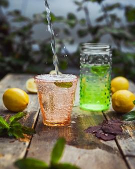 Lemoniada i składniki w szkle i słoju na stole drewnianym i stoczni. widok z boku.
