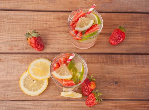 Lemoniada lub koktajl mojito z cytryną, truskawkami i miętą, zimnym napojem orzeźwiającym lub napojem z lodem.