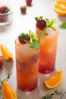 Lemoniada truskawkowa ze świeżymi owocami pomarańczy i miętą. świeże letnie koktajle owocowe.
