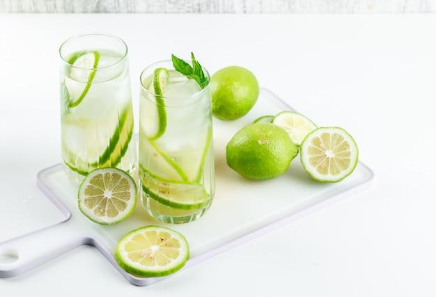 Lemoniada w szklankach z cytryną, bazylią, deską do krojenia wysoki kąt widzenia na białym i nieczysty