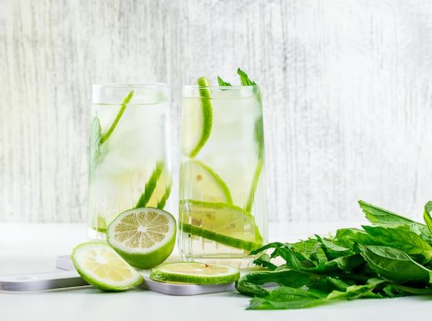 Lemoniada w szklankach z cytryną, bazylią, widok z boku deski do krojenia na białym i nieczysty