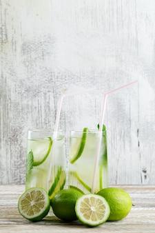 Lemoniada w szklankach z cytryną, widok z boku bazylii na drewniane i nieczysty