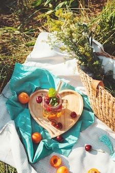 Lemoniada w szklanym kielichu i bambusowej słomie, ekologiczny letni piknik.