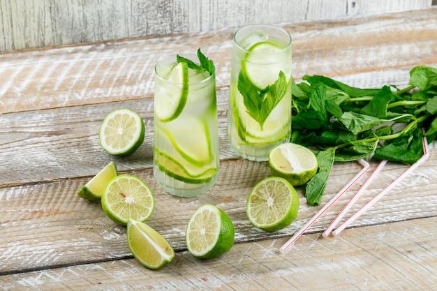 Lemoniada z cytryną, bazylią, słomkami w szklankach na drewnianym i nieczysty, wysokim kącie widoku.