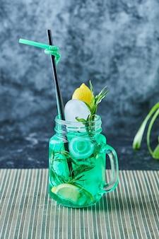 Lemoniada z cytryną, lodem, słomą i miętą na ciemnej powierzchni