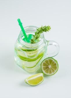 Lemoniada z cytryną, słomą, ziołami w szklanym słoiku z masonem na widok białego, wysokiego kąta.