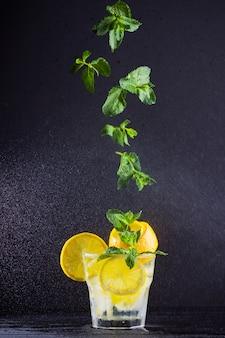 Lemoniada z latającą miętą i cytryną. lato orzeźwiający napój z cytryną na ciemnym tle. naparowana woda z cytrusami i miętą. letni koktajl w aerozolu wody. lewitacja