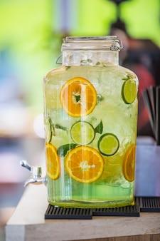 Lemoniada z limonką i pomarańczą z kostkami lodu na batonie.