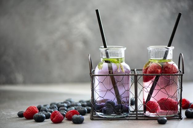 Lemoniada z malinami i jagodami w małych butelkach