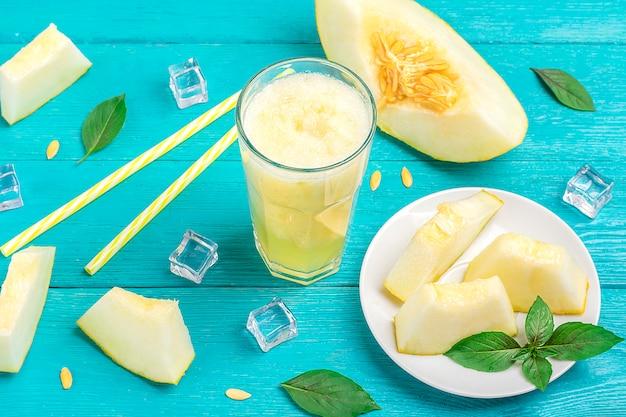 Lemoniada z melona, koktajl z lodem i bazylią w szklance, kanaliki, kawałki melona na talerzu na niebieskim drewnianym stole.